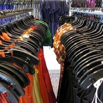 Kläder hänger på hängare i rader i affär