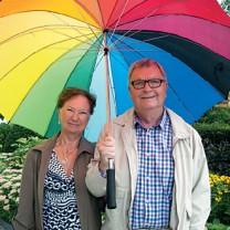Paret står utomhus under ett gigantiskt färgglatt paraply