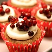 Pepparkaksmuffins med ädelostkräm i rödvita formar på vitt uppläggningsfat