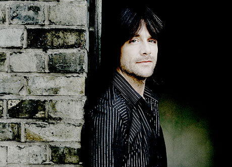 Robert Wells i svartvitrandig skjorta lutad mot vägg