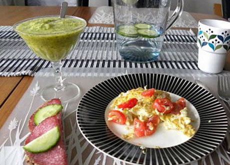 Grön smoothie i högt glas omelett på svartvit tallrik kanna gurkvatten surdegsbröd med salami