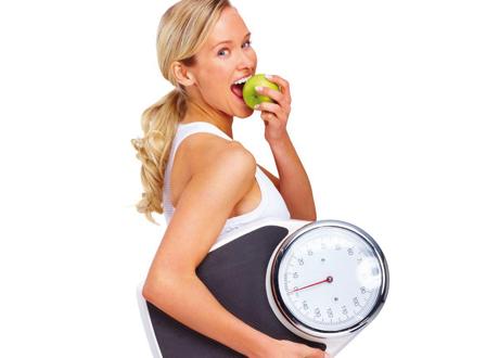 Blond kvinna äter ett äpple och håller en våg under armen