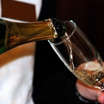 Man i frack häller upp mousserande i champagneglas