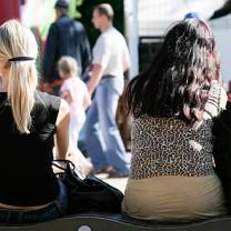 Två flickor sitter med ryggen mot kameran i en folkmassa