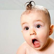 Litet barn med blött hår kammat till en tuppkam ser mycket förvånad ut