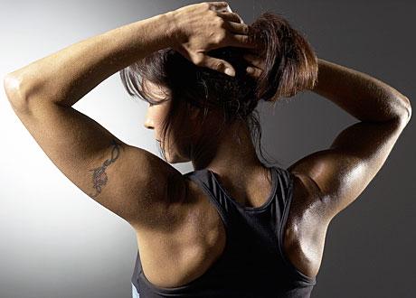 Mörkhårig muskulös kvinna i träningskläder sträcker på sig i profil