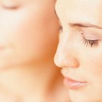 Två vackra blundande kvinnor med vacker hy och osminkade ansikten