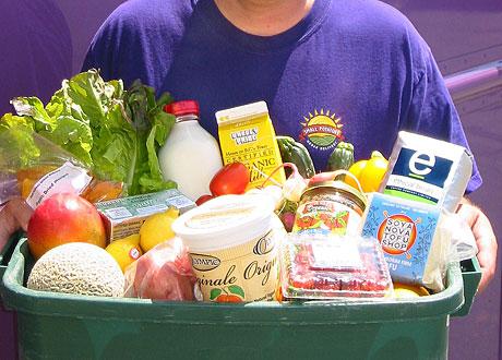 En man håller i en låda med olika sorters matförpackningar