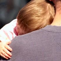 Litet barn sover mot sin pappas axel