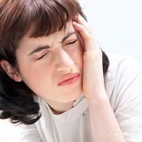 Mörkhårig kvinna blundar och tar sig åt huvudet