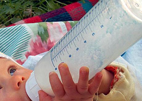 Bebis dricker ur nappflaska håller själv