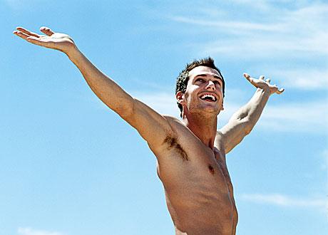 Man med bar överkropp sträcker armarna mot skyn och ser glad ut