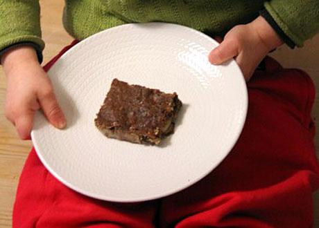 Ekologisk banan- och chokladkaka på vitt fat i barns knä