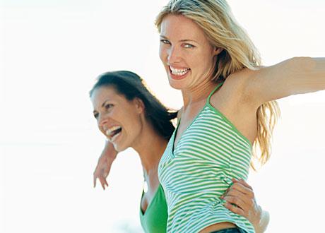 Två glada tjejer håller om varandra och ler