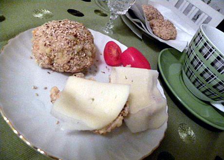 Frallor med ost och tomat på vitt fat på grönt bord