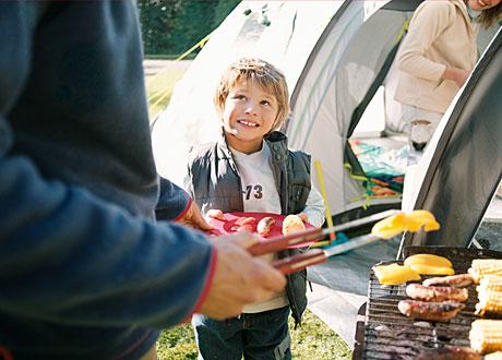 Man står vid grillen och grillar korv. Pojke väntar med tallrik. Leende kvinna syns i tält i bakgrunden.