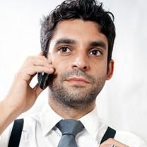 Ung man i skjorta och slips med mobiltelefon vid örat