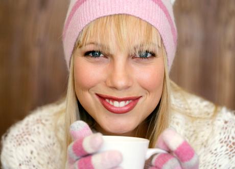 Leende vacker blond kvinna i vinterkläder rosa mössa och vantar håller i kaffekopp