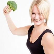 Ulrica i svarta träningskläder med broccoli i handen höjd över huvudet