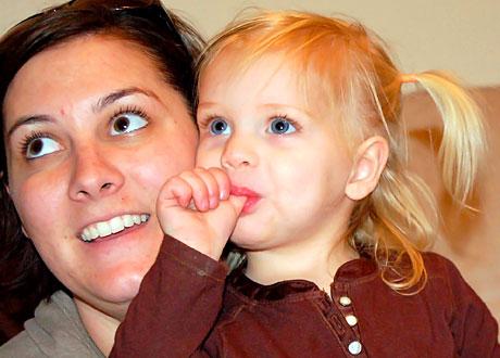 Mörkhårig mamma med blond dotter som suger på tummen i knät