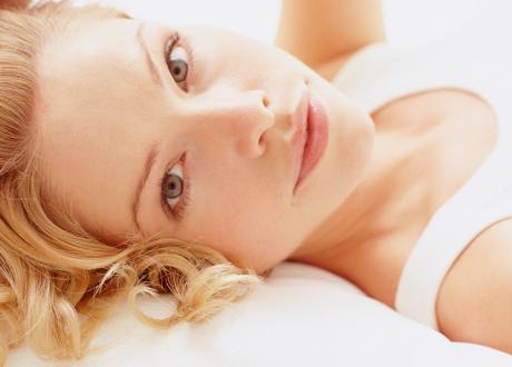 Blond tjej med vitt linne och fin hy ligger ner och tittar in i kameran i profil