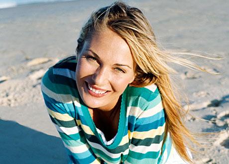 Leende blond tjej sitter på sandstrand i randig tröja
