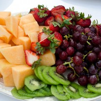 Tallrik fylld med frukt: kiwi, honungsmelon jordgubbar, vindruvor