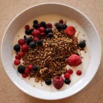 Frukostmüsli serverad med hallon och blåbär i vit skål