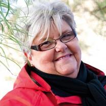 En leende Gertie står utomhus i röd jacka och svart halsduk