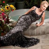 Gunilla Persson poserar likt en sjöjungfru i aftonklänning vid fontän