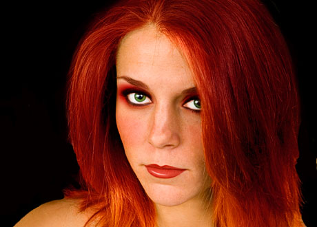 Ung tjej med färgat rött hår tittar in i kameran