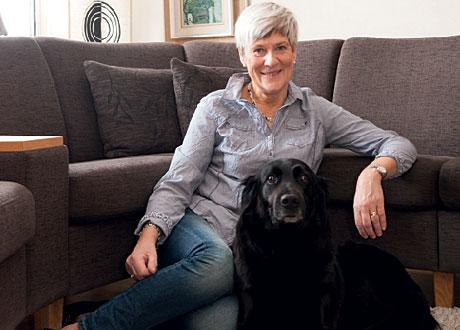 Karin sitter på golvet framför soffan med sin hund