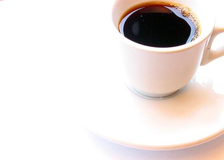 En kopp kaffe i vit kopp med vitt fat