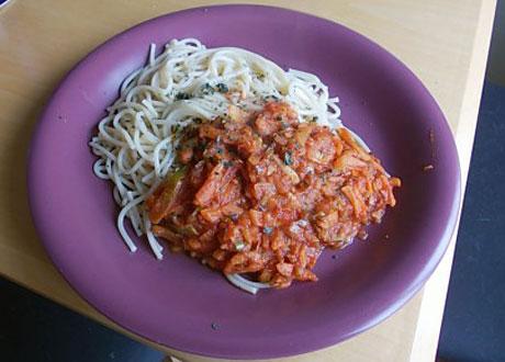 Vegetarisk pastasås serverad med spaghetti på lila tallrik
