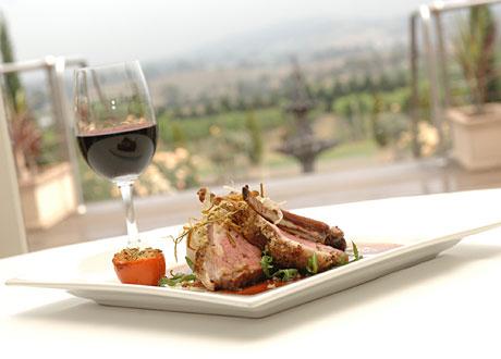 Tallrik med fint upplagd mat portion mindre på vit duk bredvid glas med rött vin
