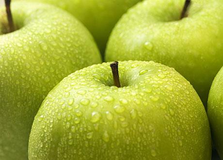 Gröna äpplen med vattendroppar på sig