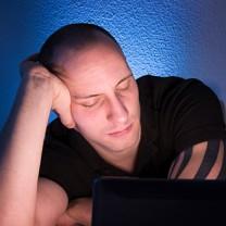 Man sitter med kutig rygg över laptop