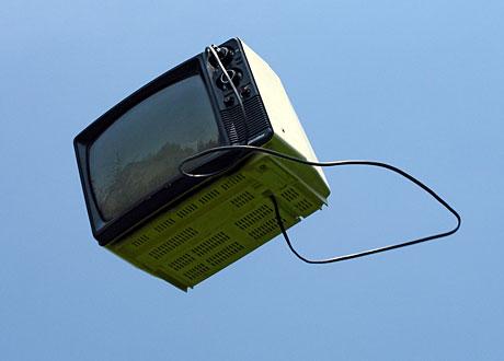 En TV modell 1970-tal flyger genom luften mot blå himmel