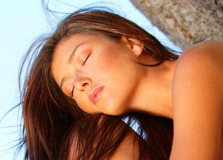 Mörkhårig kvinna med vacker och len hy blundar mot solen