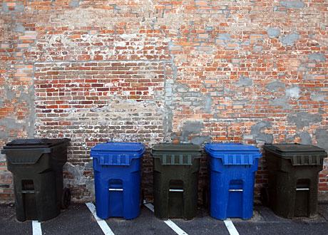 Fem återvinningsbehållare på rad mot tegelvägg