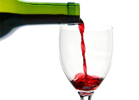 Ett vinglas fylls av rött vin i grön flaska
