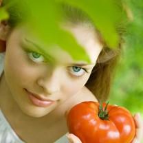 Rödhårig ung kvinna i vit blus står i grönska med tomat i handen