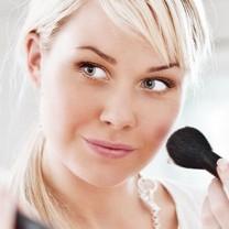 Blond kvinna som sminkar sig i spegeln