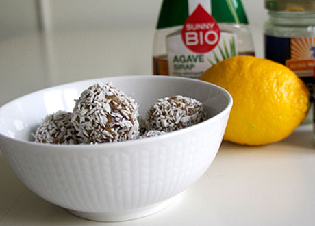 raw food-bollar liggande i vit skål med citron bredvid