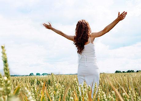 Kvinna står på fält med armarna uppåt