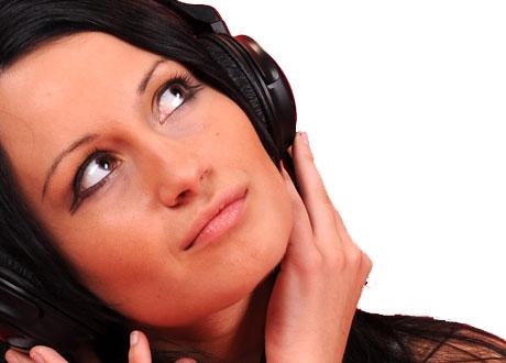 Brunett lyssnar på musik i stora hörlurar