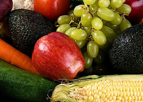 Frukter i en hög, avokado, gröna vindruvor, majs och äpple