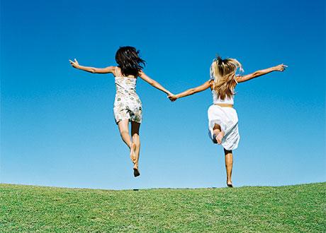 Två kvinnor som skuttar hand i hand över äng