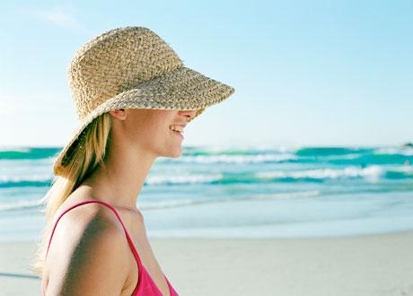 Kvinna i solhatt på en strand