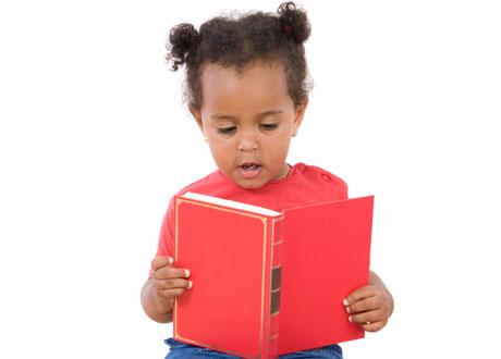 Liten flicka sitter och läser